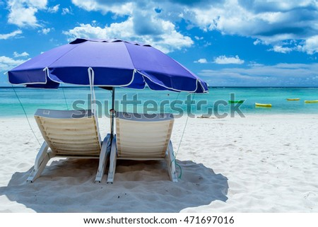 A pair of beach chairs under an umbrella on a deserted beach with white sand.