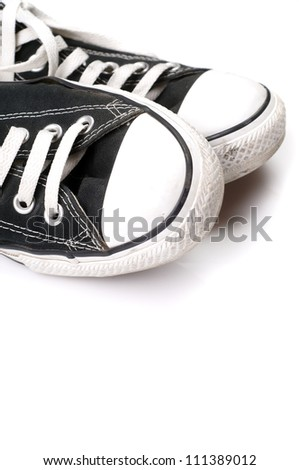 A pair of black canvas sneakers on white - stock photo