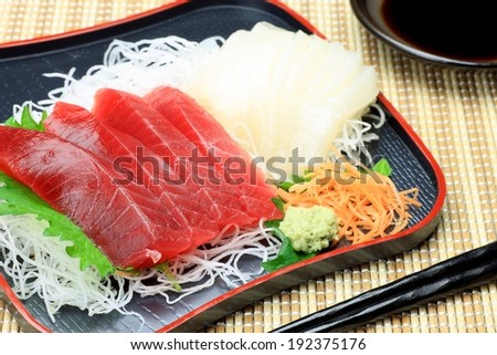 A pair of black chopsticks near a dinner plate with a variety of noodles and meat. - stock photo