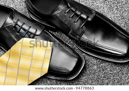 A pair of black leather dress shoes with a yellow necktie - stock photo