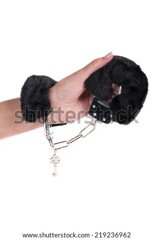 a pair of black sexy fluffy handcuffs on a white background  - stock photo