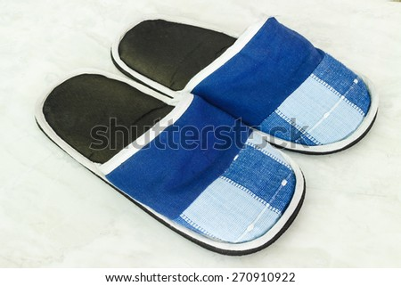 A pair of blue slippers on a ground - stock photo