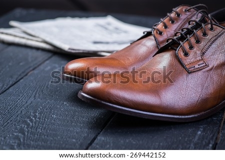 A pair of brown leather shoes with vintage camera and newspaper on a black wooden floor