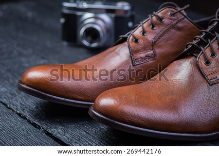 A pair of brown leather shoes with vintage camera on a black wooden floor - stock photo