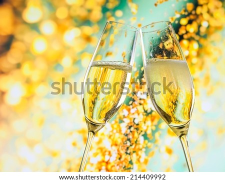 a pair of champagne flutes with golden bubbles make cheers on golden light background with space for text - stock photo