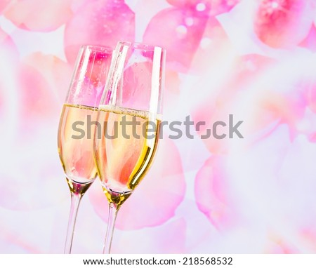 a pair of champagne flutes with golden bubbles on blur petals of roses background love concept - stock photo
