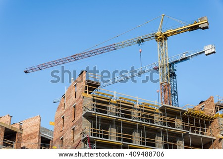 A pair of construction cranes in building site on blue sky background