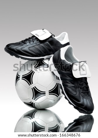 A pair of cool football boots standing on a ball on a reflective surface. - stock photo