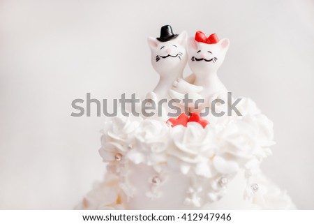 a pair of cute cats on the top of a beautiful white creamy wedding cake - stock photo