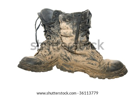 A pair of dirty hiking boots isolated over white - stock photo