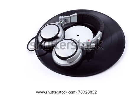 A pair of DJ style headphones on top of a vinyl record isolated on white.