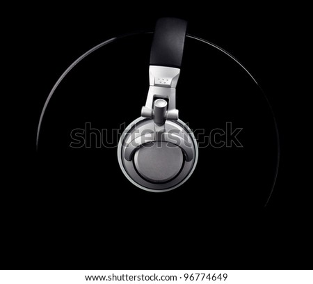 A pair of DJ style headphones wrapped around a record isolated on black. - stock photo