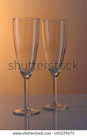 A pair of empty champagne glasses in warm studio lighting