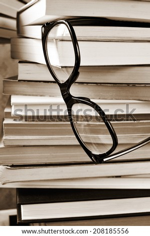 a pair of eyeglasses on a pile of books, in black and white - stock photo