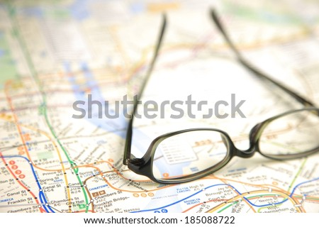 A pair of eyeglasses sitting on a map of the New York City subway system. - stock photo
