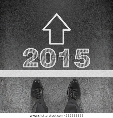 A pair of feet on a tarmac road at the beginning of the new year 2015. A concept of starting point.  - stock photo