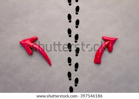 A pair of feet standing on a tarmac road with red arrow  in two different directions for the concept of making decision at the crossroad. - stock photo