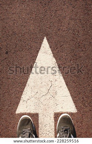 A pair of feet standing on street on white direction arrow.Toned photo, low contrast. - stock photo