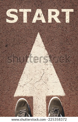 A pair of feet standing on street, white direction arrow, start concept. Toned concept , low contrast. - stock photo