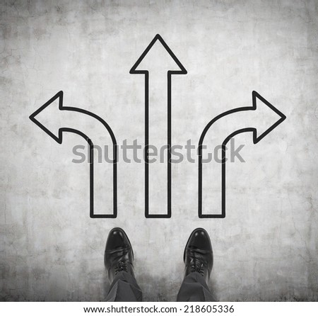 A pair of feet standing on the road with drawn arrows in three different directions. Decision making concept. - stock photo