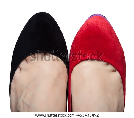 A pair of female legs in shoes with different colors - stock photo