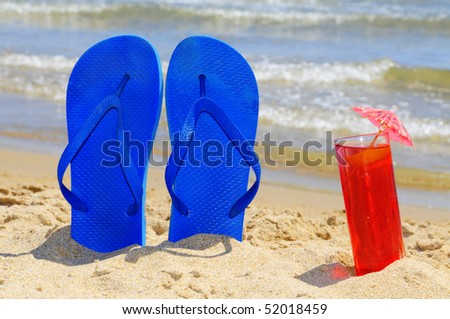 a pair of flip-flops and a cocktail on the beach