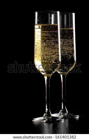a pair of flutes of champagne with golden bubbles on black wood background and space for text - stock photo