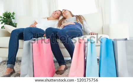 A pair of girls sitting on the couch together after having a hard day of shopping - stock photo