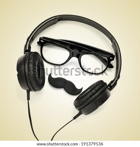 a pair of glasses, a mustache and a pair of headphones on a beige background, depicting a hipster guy - stock photo