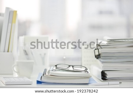 A pair of glasses sitting on a stack of books. - stock photo