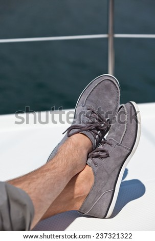 A pair of hairy man legs in pants and topsiders on white yacht deck. Yachting - stock photo