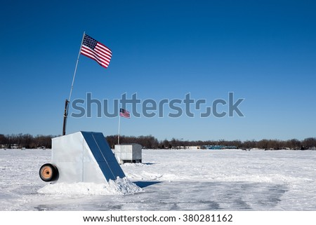 A pair of ice shanties on a frozen lake flying American flags.  Copy space in the sky.  Concepts could include fishing, patriotism, culture, winter, nature, and others.