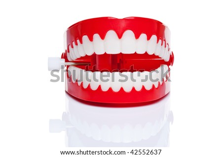 A pair of joke wind up chattering teeth on a pure white background, high resolution photo. - stock photo