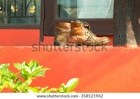 A pair of leather boots with dirt from grass lay in front of the garden resort door in sunshine morning. - stock photo