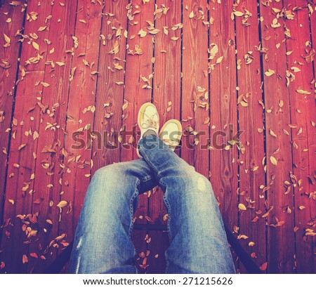 a pair of legs taken from overhead on a deck with leaves that have fallen toned with a retro vintage instagram filter app or action  - stock photo