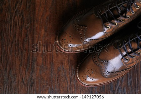 A pair of luxury brown shoes close up on wood background. - stock photo
