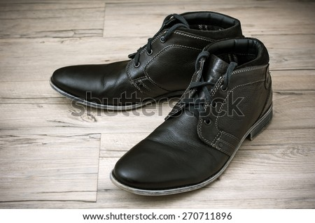 A pair of men's black leather ankle shoes placed on wooden floor