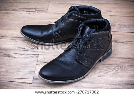 A pair of men's black leather ankle shoes placed on wooden floor - stock photo