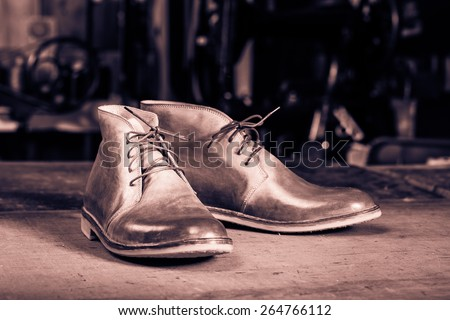 A pair of men's leather shoes in the shoemaker's workshop on working desk. Monochrome cream tone. Black and white photography. - stock photo