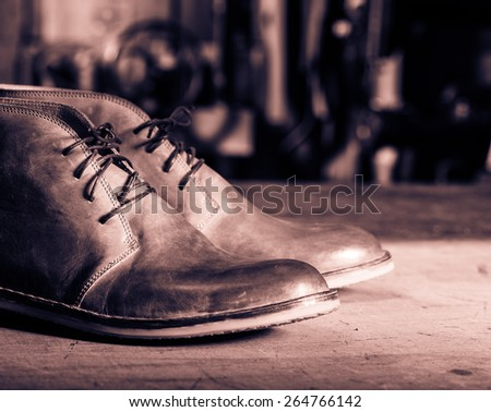 A pair of men's leather shoes in the shoemaker's workshop on working desk.Monochrome cream tone. Black and white photography. - stock photo