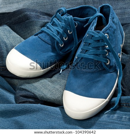 A pair of new blue shoes on a jeans - stock photo