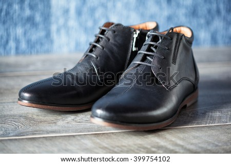 a pair of new leather men's shoes on a wooden background - stock photo