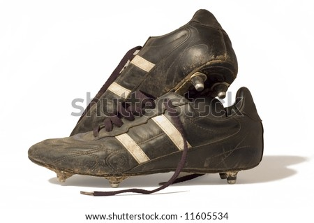 A pair of old football boots, showing signs of good use and age - stock photo