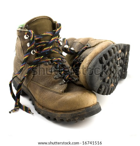 a pair of old, well-worn, hiking boots, brown with colorful laces and some mud, isolated on white - stock photo