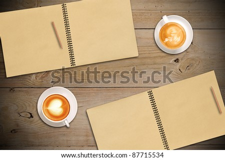 A pair of open vintage sketchbooks with pencils and a cups of coffee on old wooden table