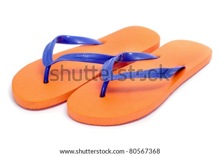 a pair of orange flip-flops on a white background - stock photo