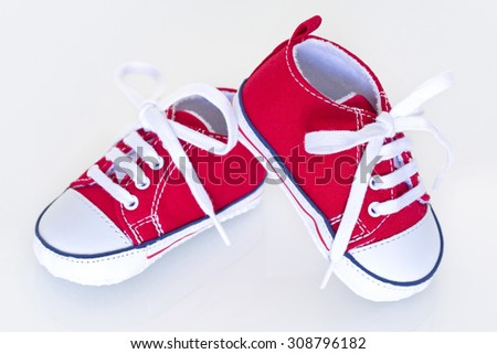 A pair of red baby shoes on a white background