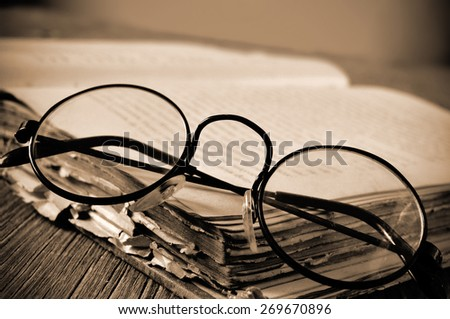 a pair of round-framed eyeglasses on an old book, on a rustic wooden table, in sepia toning and slight vignette added - stock photo