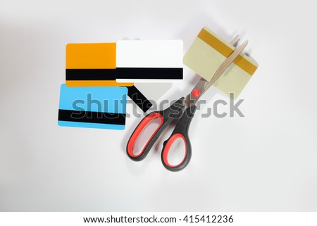 A pair of scissors cutting a credit card in half over a white background - stock photo