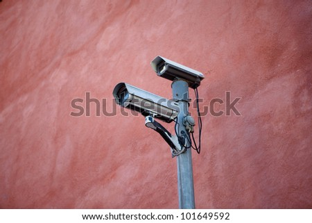 A pair of security cameras on a red wall - stock photo
